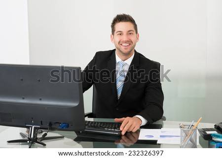 Portrait of happy young businessman using computer at desk in office - stock photo