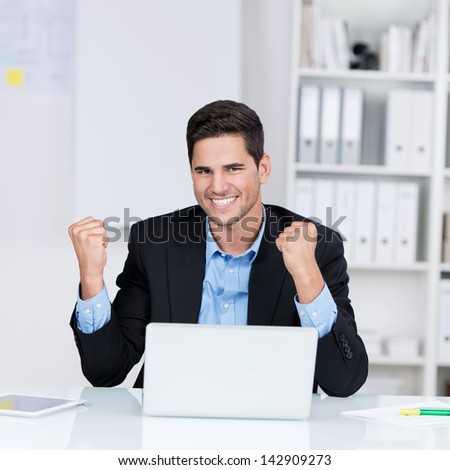Portrait of happy young businessman with laptop celebrating victory at desk in office - stock photo