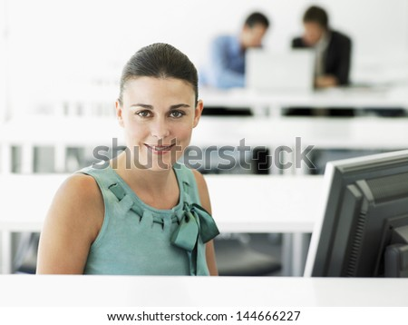 Portrait of happy young businesswoman at computer desk with male colleagues in background - stock photo