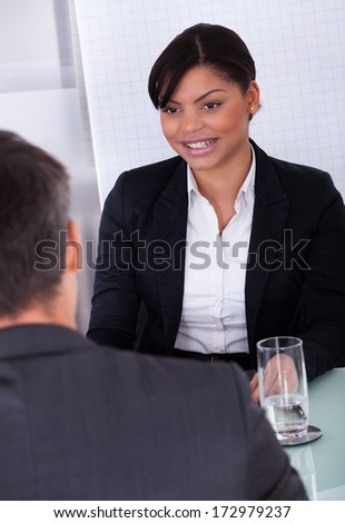 Portrait Of Happy Young Businesswoman Looking At Mature Businessman - stock photo