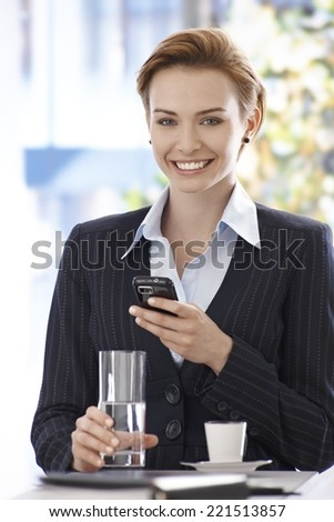 Portrait of happy young businesswoman using mobilephone, drinking water and coffee. - stock photo