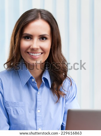 Portrait of happy young businesswoman working with laptop at office - stock photo