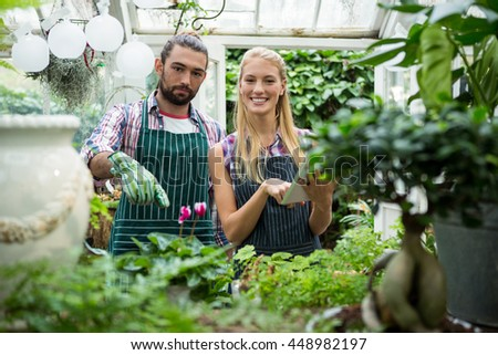 Portrait of happy young colleagues with digital tablet standing by plants at greenhouse - stock photo