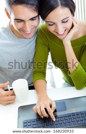 Portrait of happy young couple browsing internet at home - stock photo