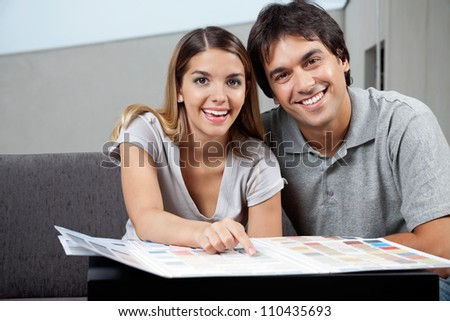 Portrait of happy young couple choosing paint colors from swatch chart - stock photo