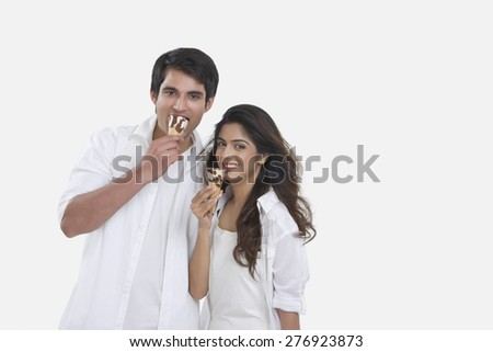 Portrait of happy young couple eating ice-cream cones isolated over white background - stock photo