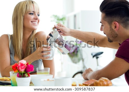 Portrait of happy young couple enjoying breakfast in the kitchen. - stock photo