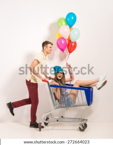 Portrait of happy young couple having fun. Girl sitting in shopping cart and keeping color balloons in hand. Guy rolling trolley. - stock photo