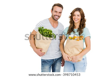 Portrait of happy young couple holding bag of vegetables on white background - stock photo