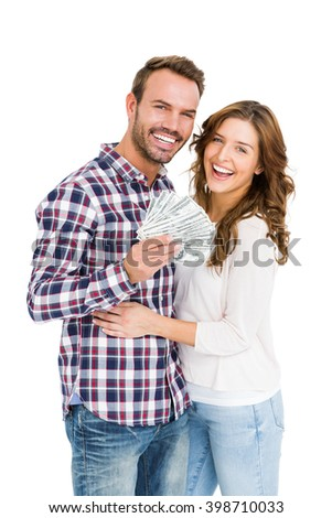 Portrait of happy young couple holding fanned out currency note on white background - stock photo