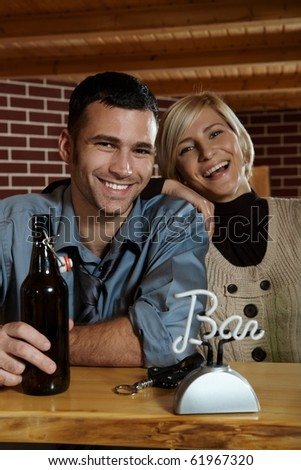 Portrait of happy young couple in pub, laughing at camera, drinking beer.? - stock photo