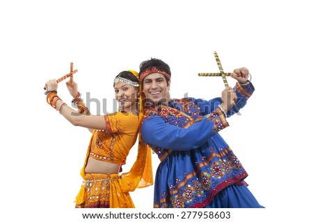 Portrait of happy young couple in traditional wear standing back to back while performing Dandiya Raas over white background - stock photo