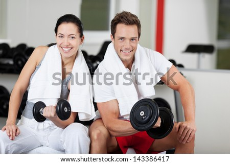 Portrait of happy young couple lifting dumbbells in gym - stock photo