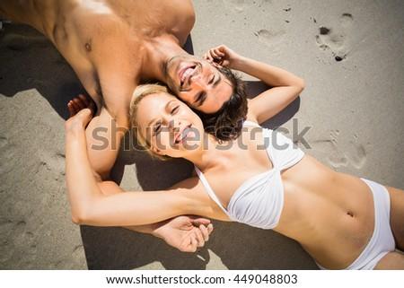 Portrait of happy young couple lying on beach - stock photo