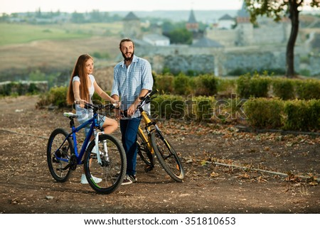 Portrait of happy young couple of bicyclists smiling in the street - stock photo