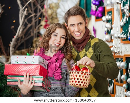 Portrait of happy young couple shopping presents in Christmas store - stock photo