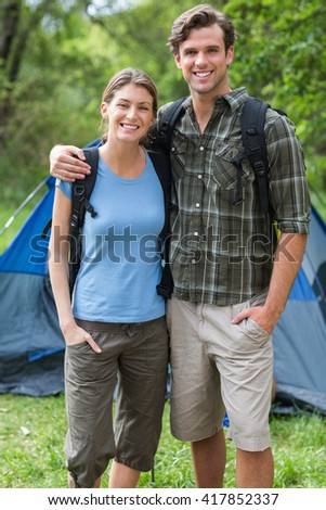 Portrait of happy young couple standing against tent in forest - stock photo