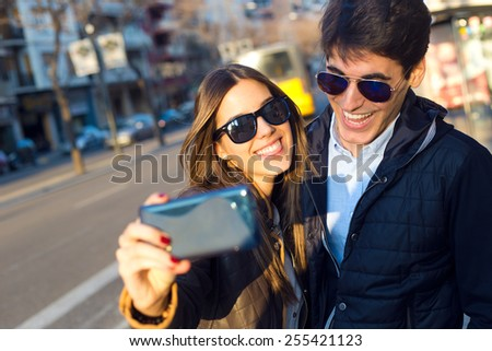 Portrait of happy young couple taking selfies with smartphone. - stock photo