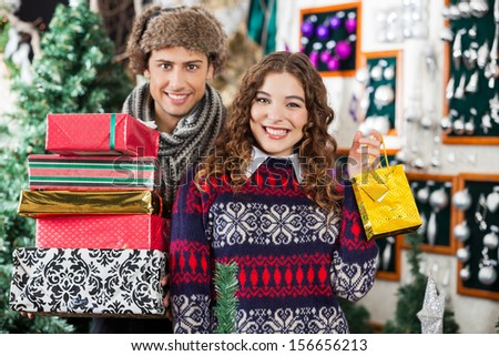 Portrait of happy young couple with Christmas presents standing together at store - stock photo