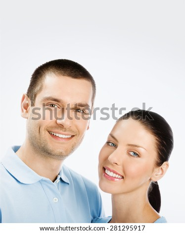 Portrait of happy young couple, with copyspace blank area for text or slogan, on grey background - stock photo