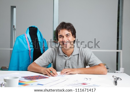 Portrait of happy young dressmaker working on rough outline designs at workshop - stock photo
