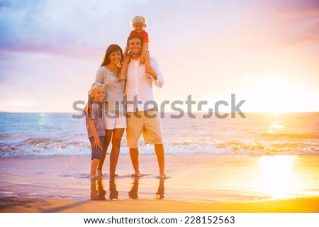 Portrait of Happy Young Family at Sunset - stock photo