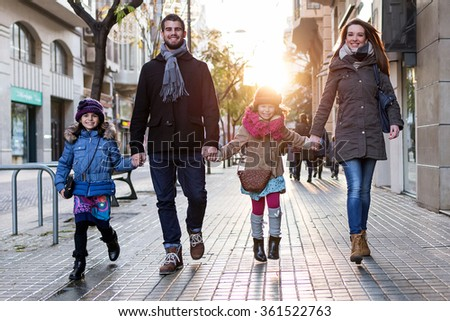 Portrait of happy young family having fun in the street. - stock photo
