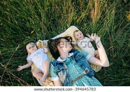 Portrait Of Happy young Family spending time outdoor on a summer day. Mother and Funny twins sisters newborn babies lying on grass  - stock photo