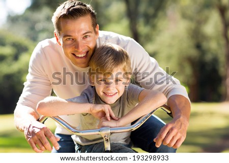 portrait of happy young father and son on a bike - stock photo