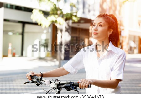 Portrait of happy young female bicyclist riding in city - stock photo