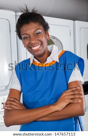 Portrait of happy young female helper standing with arms crossed in laundry - stock photo
