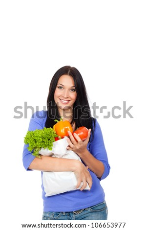 Portrait of happy young female holding a shopping bag full of vegetables isolated on white background - stock photo