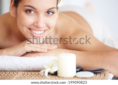 Portrait of happy young female looking at camera in spa salon - stock photo