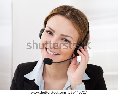 Portrait Of Happy Young Female Operator With Headphones - stock photo