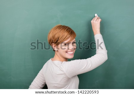 Portrait of happy young female professor writing on chalkboard while looking over shoulder - stock photo