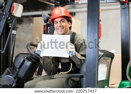 Portrait of happy young forklift driver displaying blank placard - stock photo