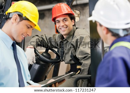 Portrait of happy young forklift driver with supervisor holding clipboard at warehouse - stock photo