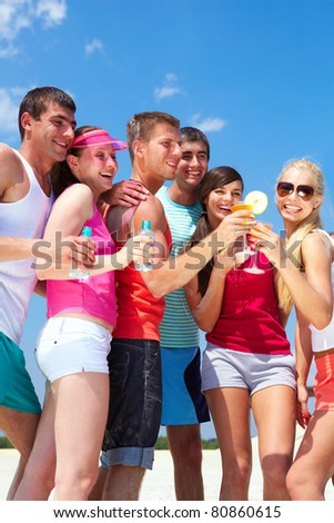 Portrait of happy young friends holding cocktails during beach party - stock photo