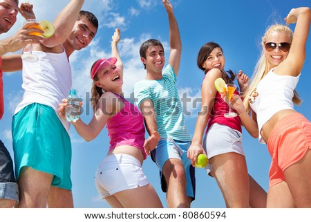 Portrait of happy young friends with cocktails dancing at beach party - stock photo