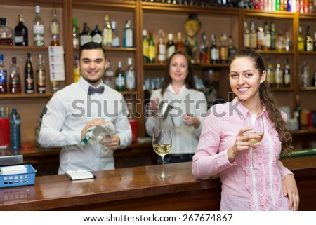 Portrait of happy young girl at counter in bar flirting with handsome barman - stock photo