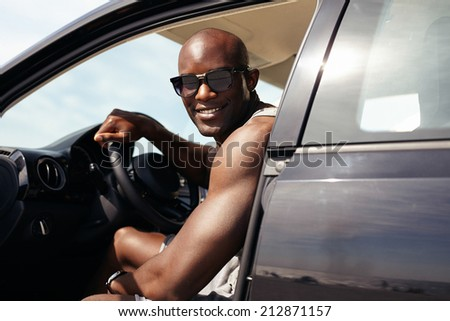 Portrait of happy young guy in his car looking at camera smiling. African male model wearing sunglasses. Muscular man on road trip.  - stock photo