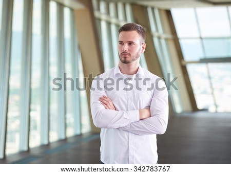 portrait of happy young handsome hipster business man with beard at modern office space interior - stock photo
