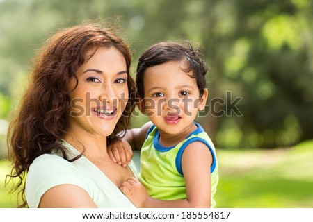 portrait of happy young indian mother and baby boy outdoors - stock photo