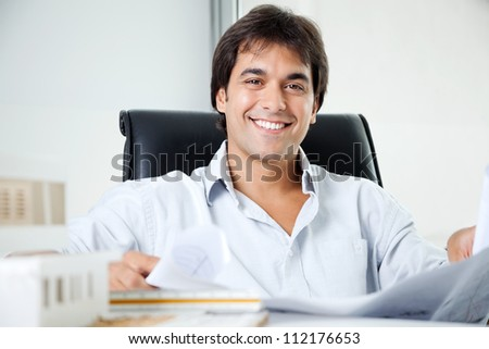 Portrait of happy young male architect with blueprint sitting in office chair - stock photo