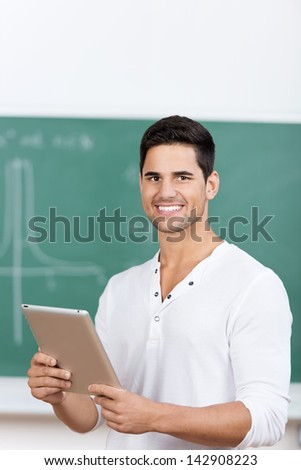 Portrait of happy young male student holding digital tablet in classroom - stock photo