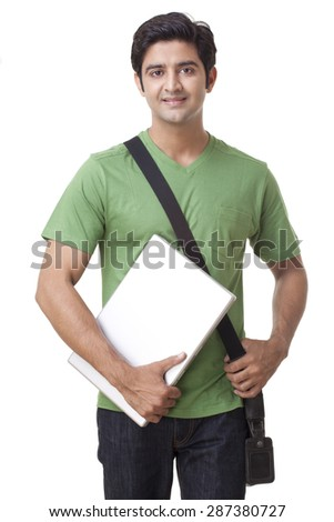 Portrait of happy young male student holding laptop - stock photo