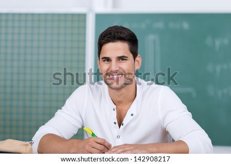 Portrait of happy young male student in classroom - stock photo