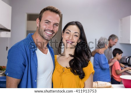 Portrait of happy young man and young woman standing in kitchen - stock photo