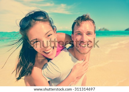 Portrait of happy young man giving piggyback ride to woman at beach. Excited couple are enjoying their summer vacation. Multiethnic tourists are having fun on shore. - stock photo