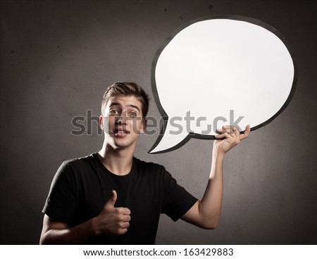 portrait of happy young man holding a speech bubble - stock photo